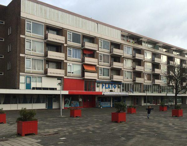 aanzicht van de bestaande situatie van de senecaflat in amsterdam voor de renovatie met rode plantenbakken en een kind op de parkeerplaats