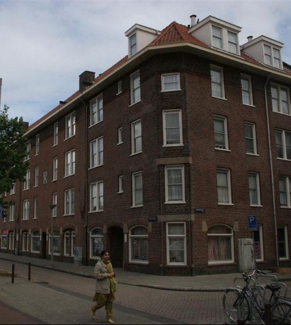 de huizen aan de hoek van de tugelaweg in de bestaande situatie voor de renovatie met een wijkbewoner lopend over de stoep