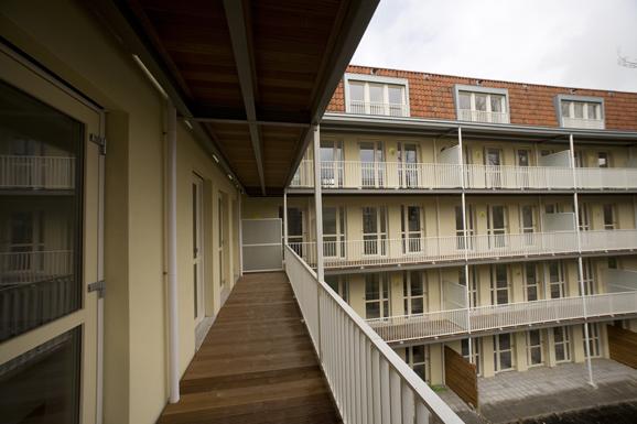 Vernieuwde galerij en balkons van de gorontaloflat in amsterdam met gele, witte en oranje details