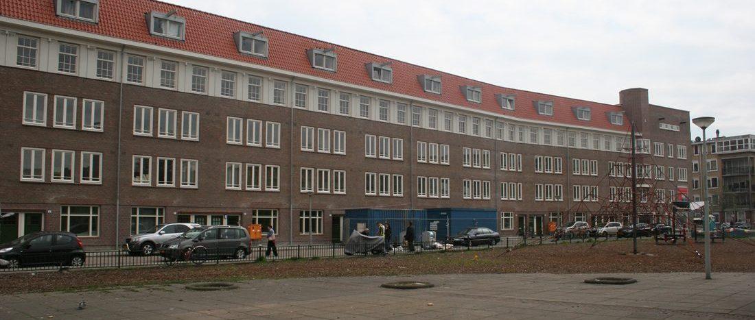Compleet aanzicht van de voorkant van het gerenoveerde appartementencomplex in de Gorontalostraat in Amsterdam met speeltuin
