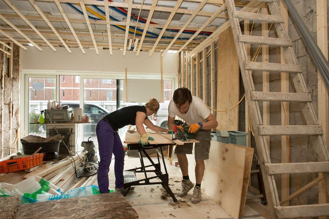 aan de klarenstraat een man een een vrouw die aan het werken zijn met een houten plaat in een toekomstige woning
