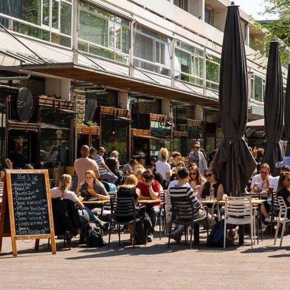 mensen op stoelen op een teras van het cafe bokaal aan de nieuwemarkt in rotterdam